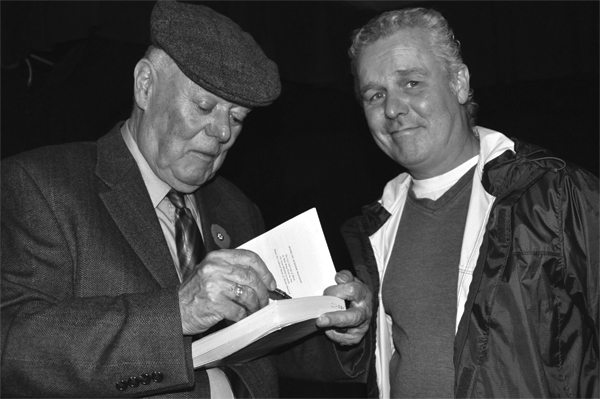 Alistair MacLeod signs a dedication for author Bruce Johnson at a Ship book launch.