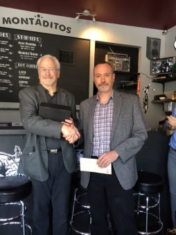 Ian McKay (left) handing Between the Lines (right) the $10,000 award.